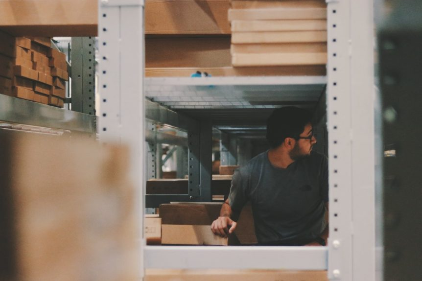 warehouse-worker-under-a-bunch-of-large-shelves